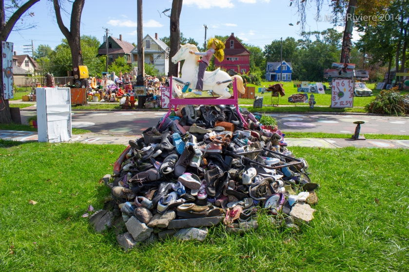 A mound of shoes crowned by a child's riding horse and a doll astride it